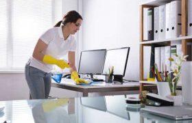 Eine Reinigungskraft reinigt den Schreibtisch in einem Büro
